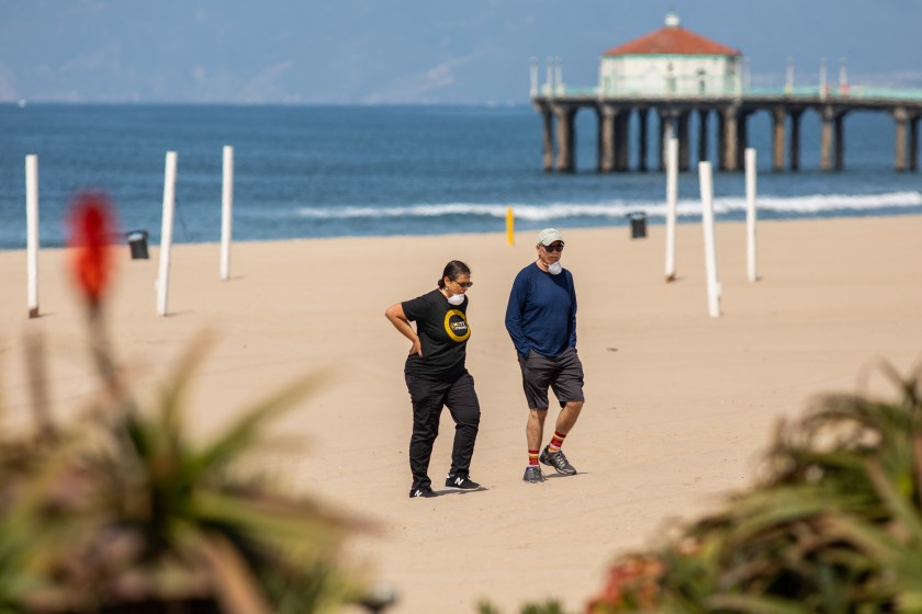 Above, two people on the sand at Manhattan Beach in late March 2020 despite beach closures. (Jay L. Clendenin/ Los Angeles Times)
