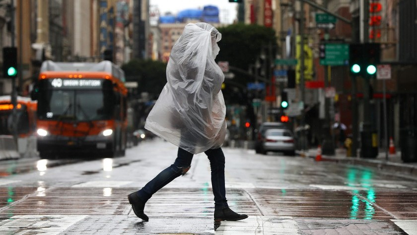 A pedestrian takes cover from the rain in downtown Los Angeles on Monday.(Christina House / Los Angeles Times)