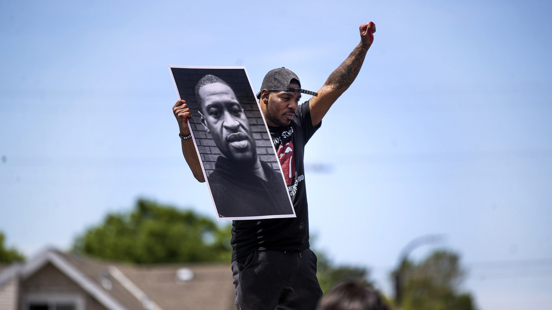 Tony L. Clark holds a photo of George Floyd outside a convenience store, Thursday, May 28, 2020, in Minneapolis. (Credit: Jerry Holt/Star Tribune/AP)