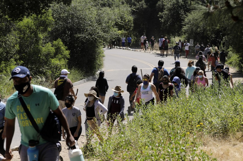 Visitors stream into and out of Eaton Canyon Natural Area on Sunday, which prompted park officials to close trails for the rest of the holiday weekend.(Myung J. Chun / Los Angeles Times)