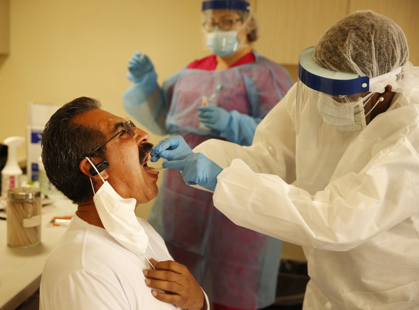 Alfredo Contreras receives an oral swab test for COVID-19 from nurse practitioner Anniesatu Newland at a walk-in coronavirus testing at St. John's Well Child and Family Center in South Los Angeles on May 18, 2020. (Al Seib / Los Angeles Times)