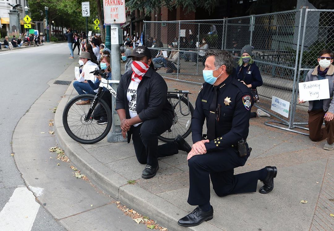 Police Chief Andy Mills takes a knee with protestors in Santa Cruz. (Shmuel Thaler)