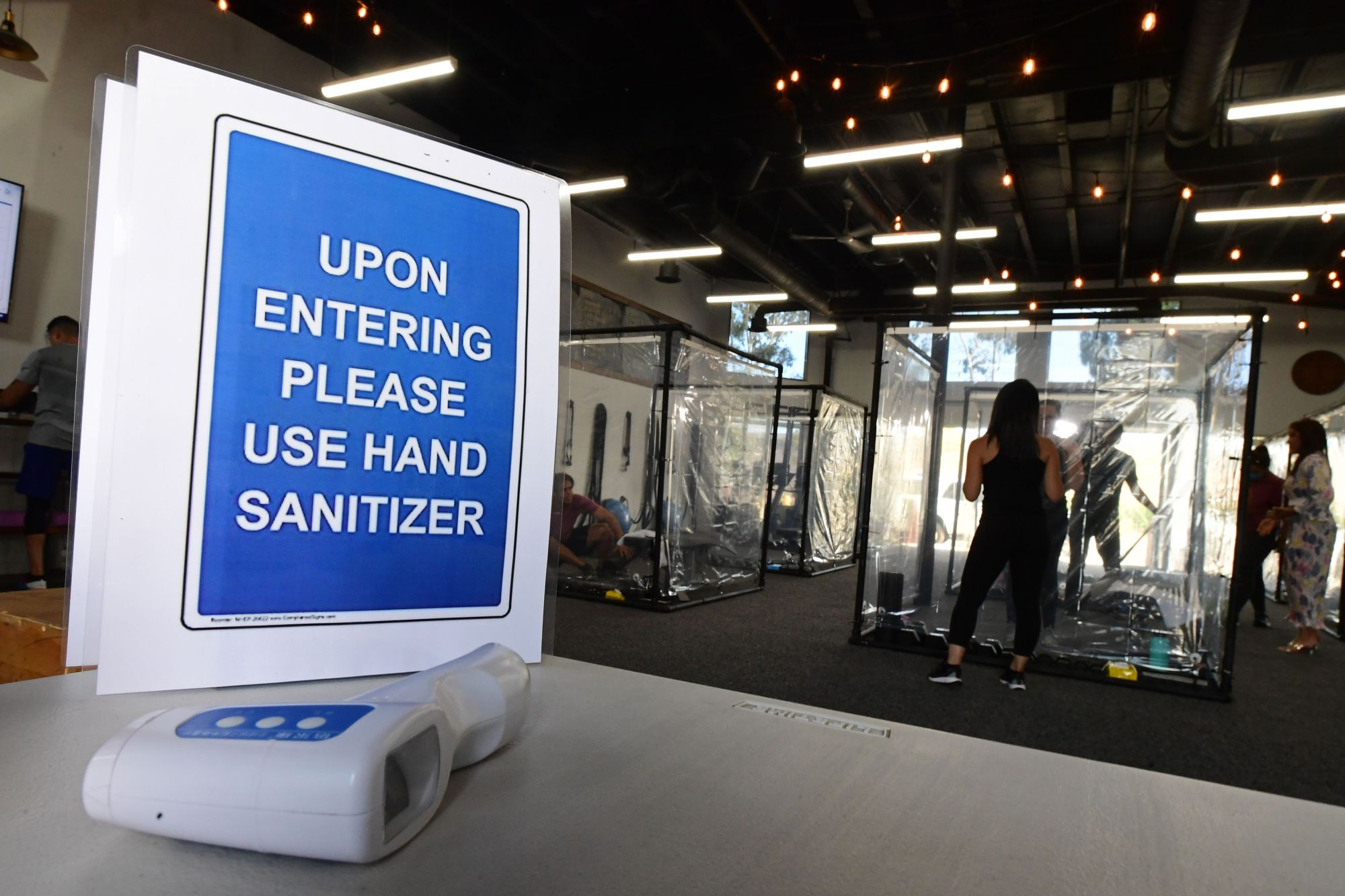 A sign is pictured as people exercise at Inspire South Bay Fitness behind plastic sheets in their workout pods while observing social distancing on June 15, 2020 in Redondo Beach, California. (FREDERIC J. BROWN/AFP via Getty Images)