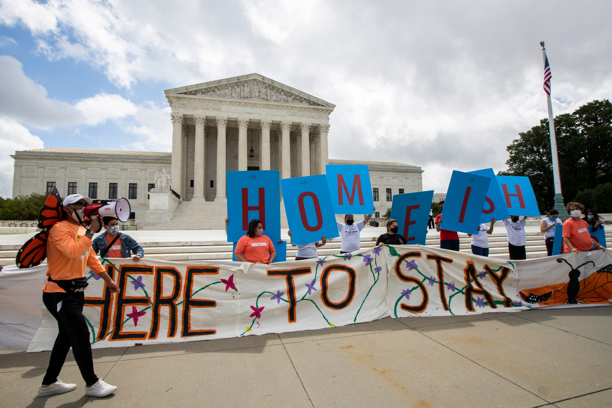 Deferred Action for Childhood Arrivals (DACA) recipient Roberto Martinez, left, celebrates with other DACA recipients in front of the Supreme Court on Thursday, June 18, 2020, in Washington. The Supreme Court rejected President Donald Trump's effort to end legal protections for 650,000 young immigrants, a stunning rebuke to the president in the midst of his reelection campaign. (AP Photo/Manuel Balce Ceneta)