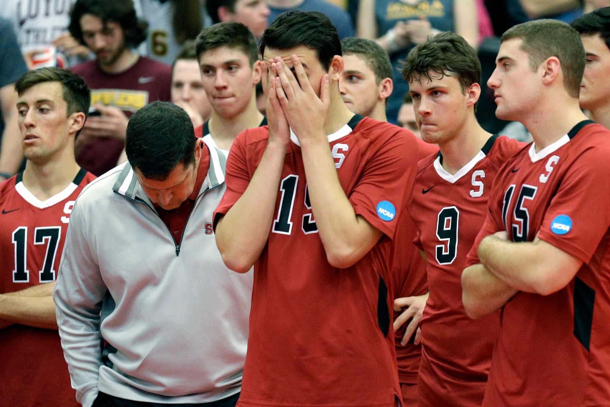 The Stanford men's volleyball head coach John Kosty, second from left, looks down as players react to a loss in the NCAA men's college volleyball championship in Chicago on May 3, 2014. (AP Photo/Nam Y. Huh, File)