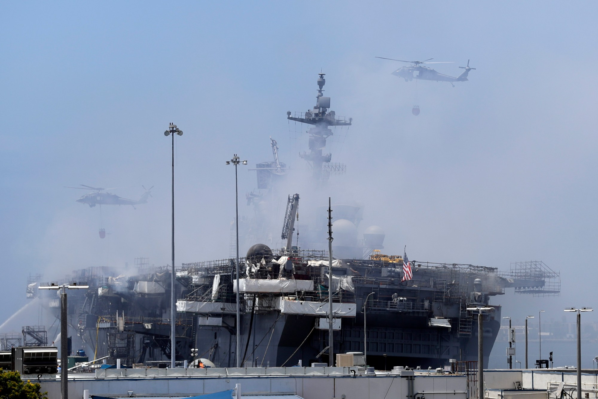 Helicopters approach the USS Bonhomme Richard as crews fight the fire on July 13, 2020, in San Diego. (AP Photo/Gregory Bull)