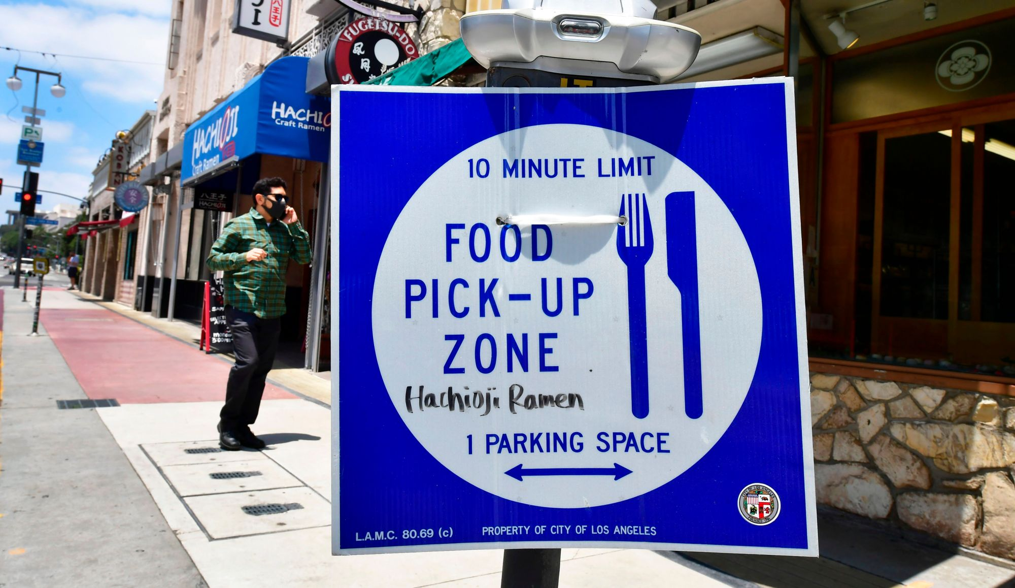 A pedestrian wearing a face mask walks past a sign for food pick-up outside a restaurant in Los Angeles on July 1, 2020, after indoor restaurants, bars and movie theaters across much of California were ordered to close for at least three weeks. (FREDERIC J. BROWN/ Getty Images)
