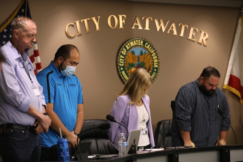 """Atwater, in California's Merced County, declared itself a """"sanctuary city"""" from the state's coronavirus stay-at-home orders. City Council members John Cale, left, Danny Ambriz, City Manager Lori Waterman and Mayor Pro Tem Brian Raymond bow their heads during the invocation at the start of a meeting on May 26. (Genaro Molina / Los Angeles Times)"""