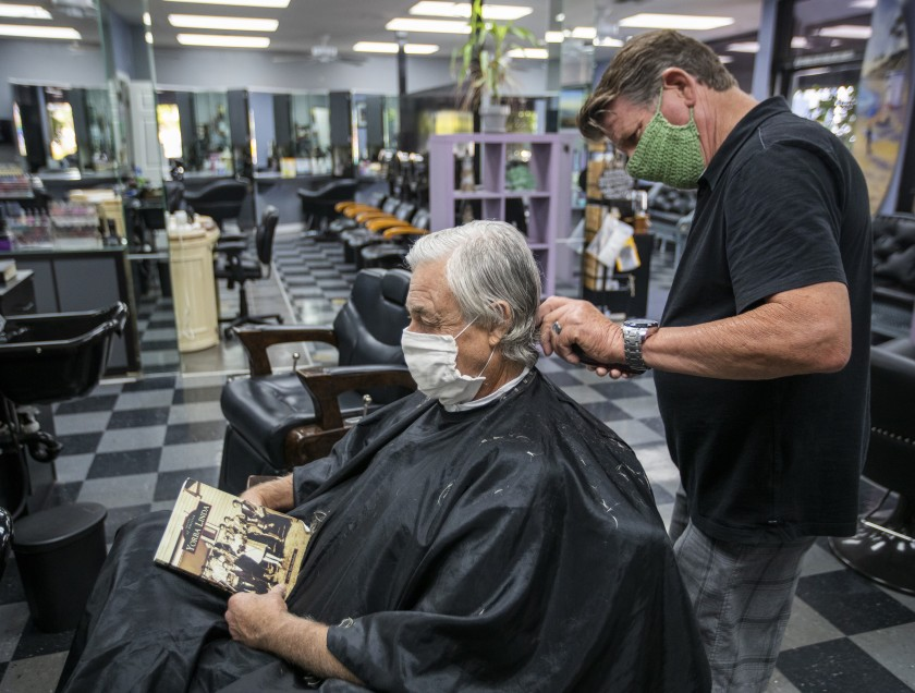 Bill Janeway, with salon owner Steve Curtis, gets a haircut in late May at Joncolby's Hair Salon in Yorba Linda.(Allen J. Schaben/Los Angeles Times)