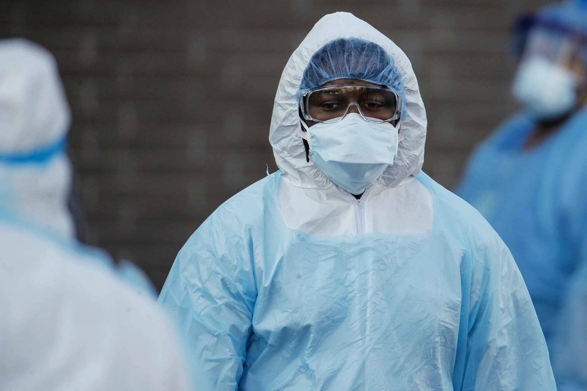 A medical worker wearing personal protective equipment pauses after wheeling a body to a refrigerated trailer serving as a makeshift morgue at Wyckoff Heights Medical Center on April 6, 2020, in New York. (AP Photo/John Minchillo)