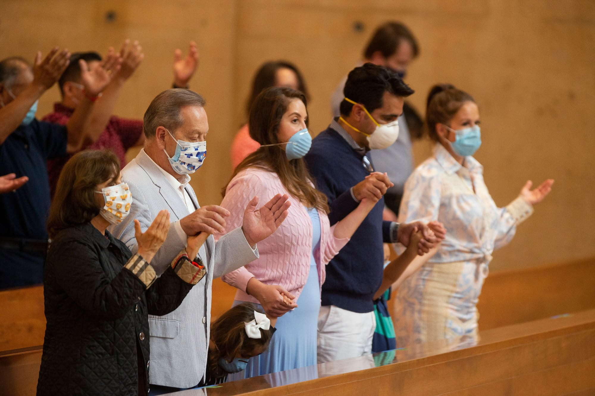 Family members hold hands as they pray at the first English Mass with faithful present at the Cathedral of Our Lady of the Angels in downtown Los Angeles, Sunday, June 7, 2020. Catholic parishes throughout the Archdiocese of Los Angeles suspended public Mass in March amid the coronavirus outbreak. (AP Photo/Damian Dovarganes)