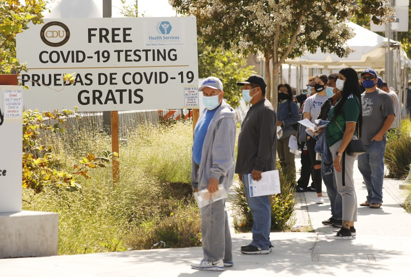 People waiting to be tested for COVID-19 stand in line outside the Charles R. Drew University of Medicine and Science in South Los Angeles on July 8, 2020. (Al Seib / Los Angeles Times)
