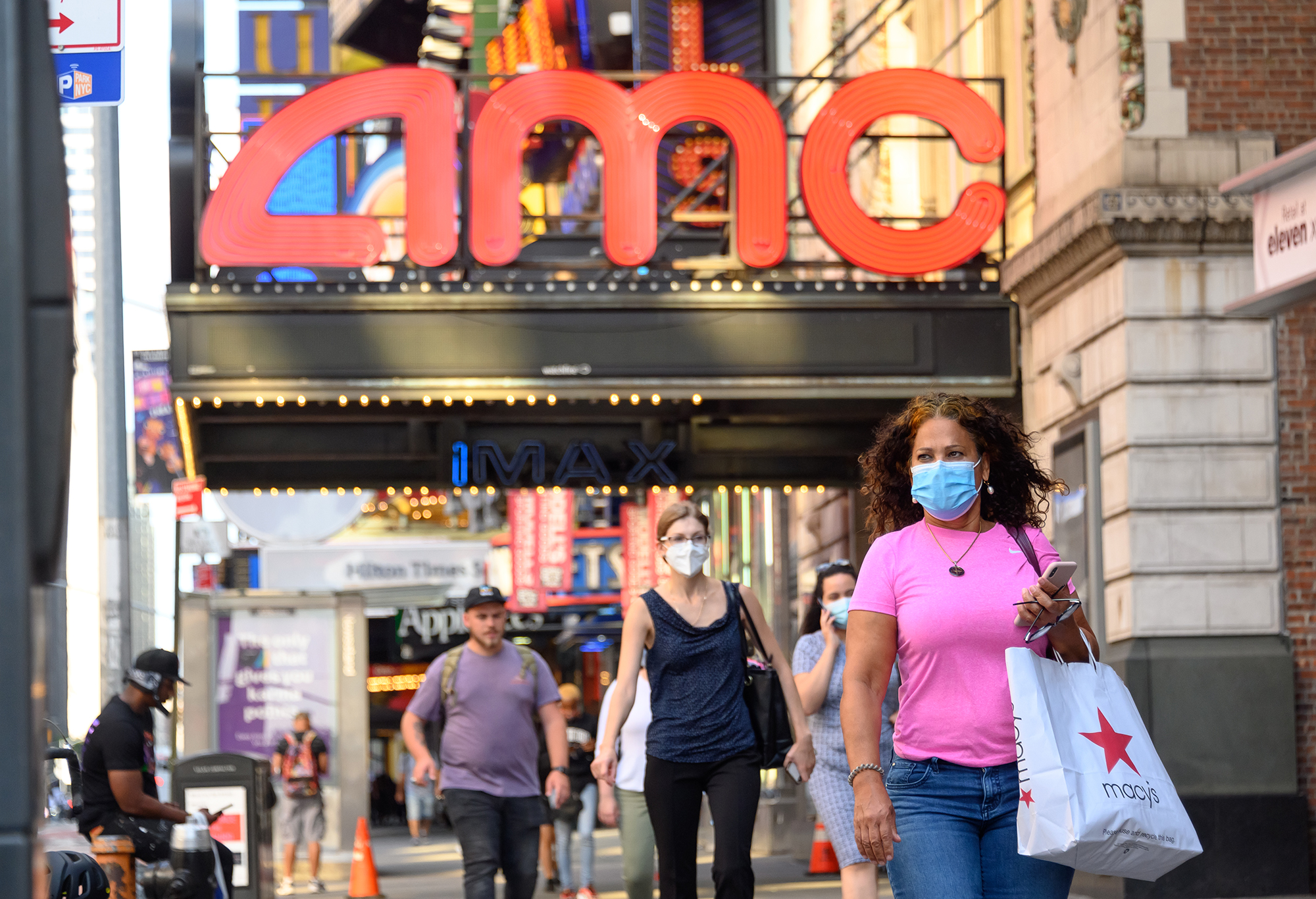 People wear protective face masks outside the AMC Empire 25 movie theater in Times Square as the city continues Phase 4 of re-opening following restrictions imposed to slow the spread of coronavirus on August 5, 2020 in New York City. (Noam Galai/Getty Images)