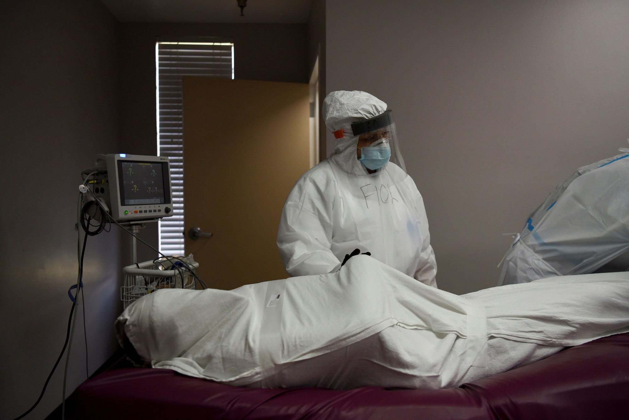 The body of a patient, who died during an intubation procedure, is prepared by Flor Trevino, 39, a nurse, to be transported to a morgue, at United Memorial Medical Center (UMMC), during the coronavirus disease (COVID-19) outbreak, in Houston, Texas, U.S., July 17, 2020. (REUTERS/Callaghan O'Hare)