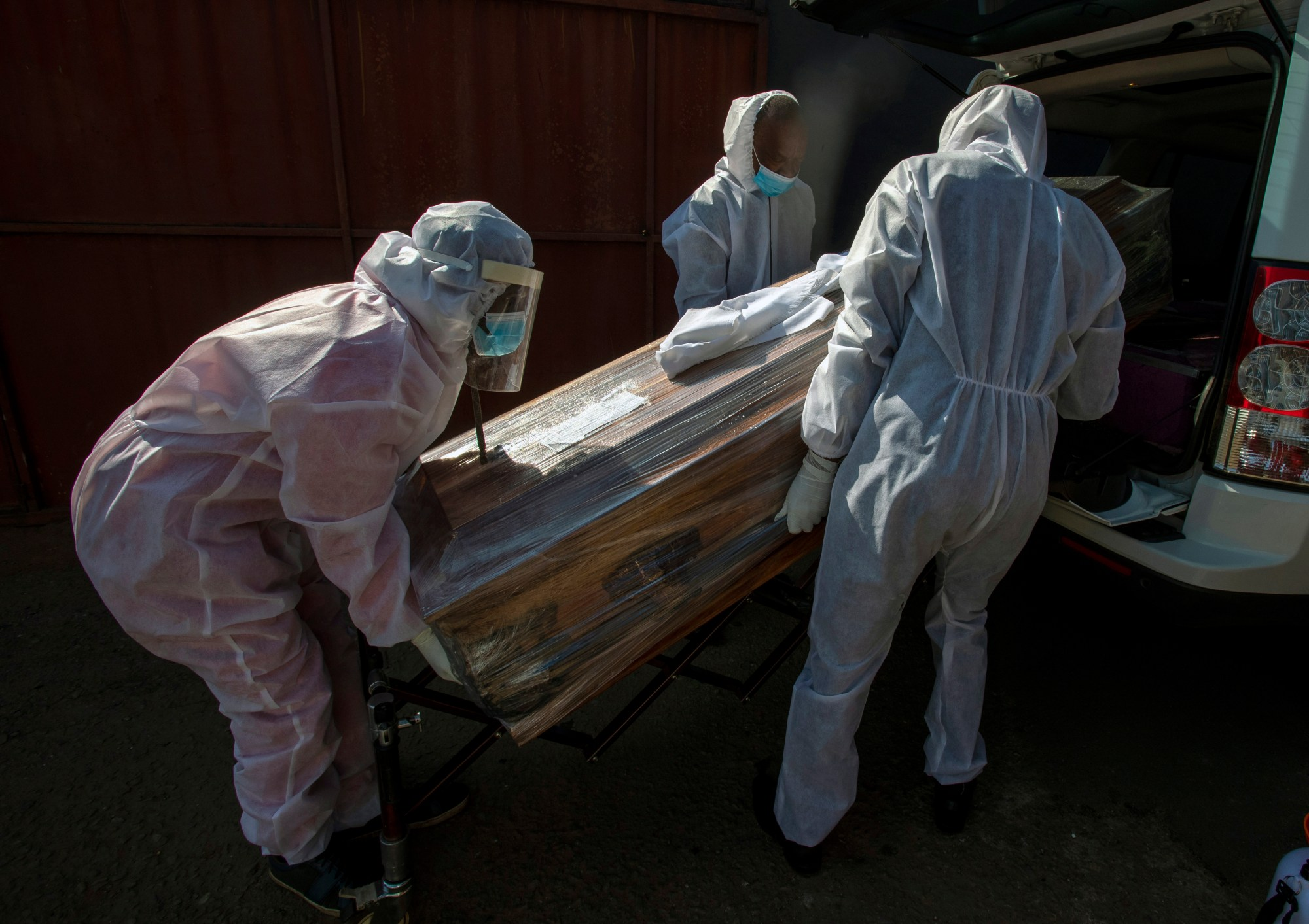 In this July 21 2020, file photo, funeral home workers in protective suits carry the coffin of a woman who died from COVID-19 into a hearse in Katlehong, near Johannesburg, South Africa. (Themba Hadebe/Associated Press)