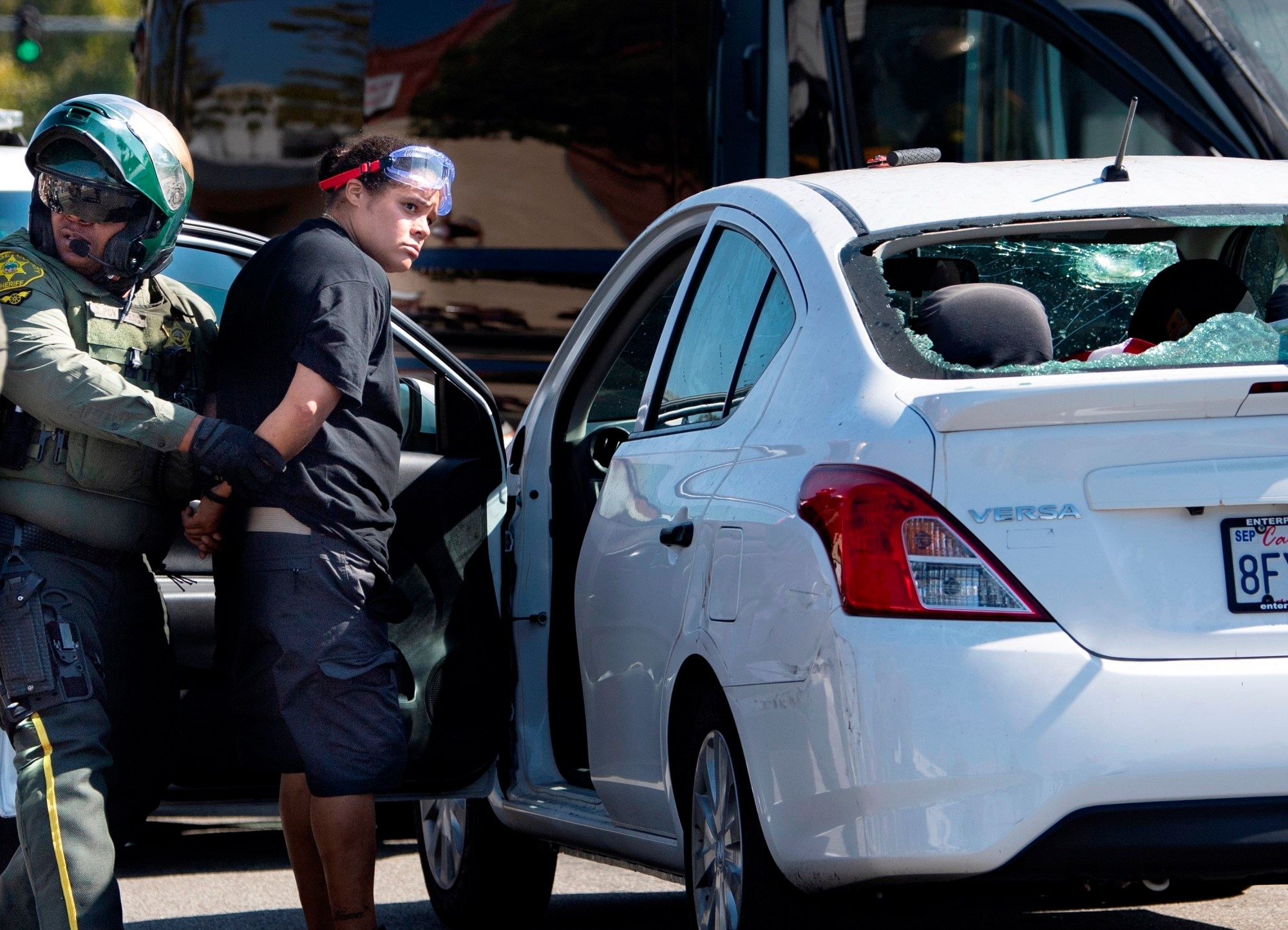 An unidentified woman is taken into custody after witnesses said she drove her car into a crowd of protesters in Yorba Linda, Calif., on Sept. 26, 2020.(Mindy Schauer/The Orange County Register via AP)