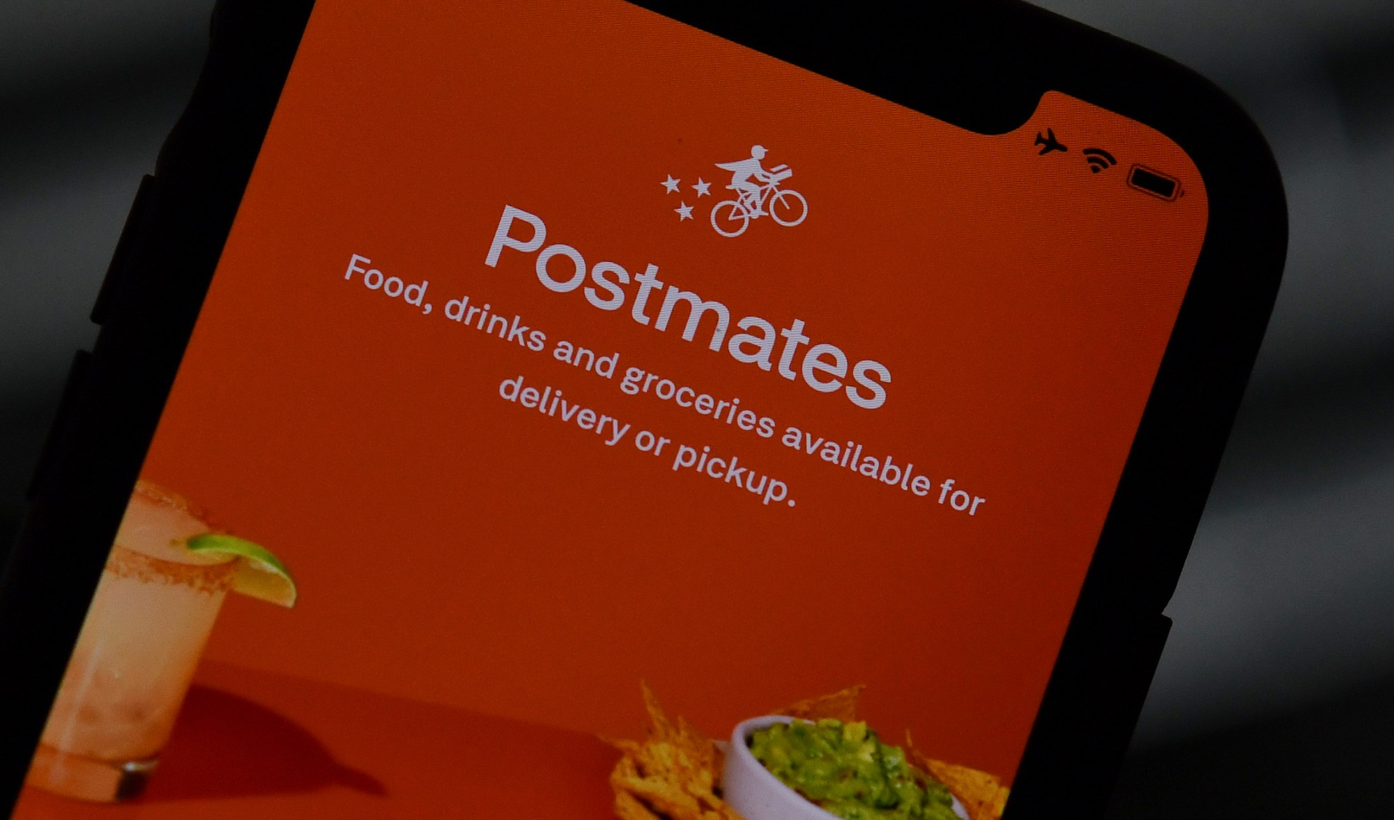 This illustration photo taken on June 30, 2020, shows the logo of delivery app Postmates on a smartphone screen in Los Angeles. (Chris Delmas / AFP / Getty Images)