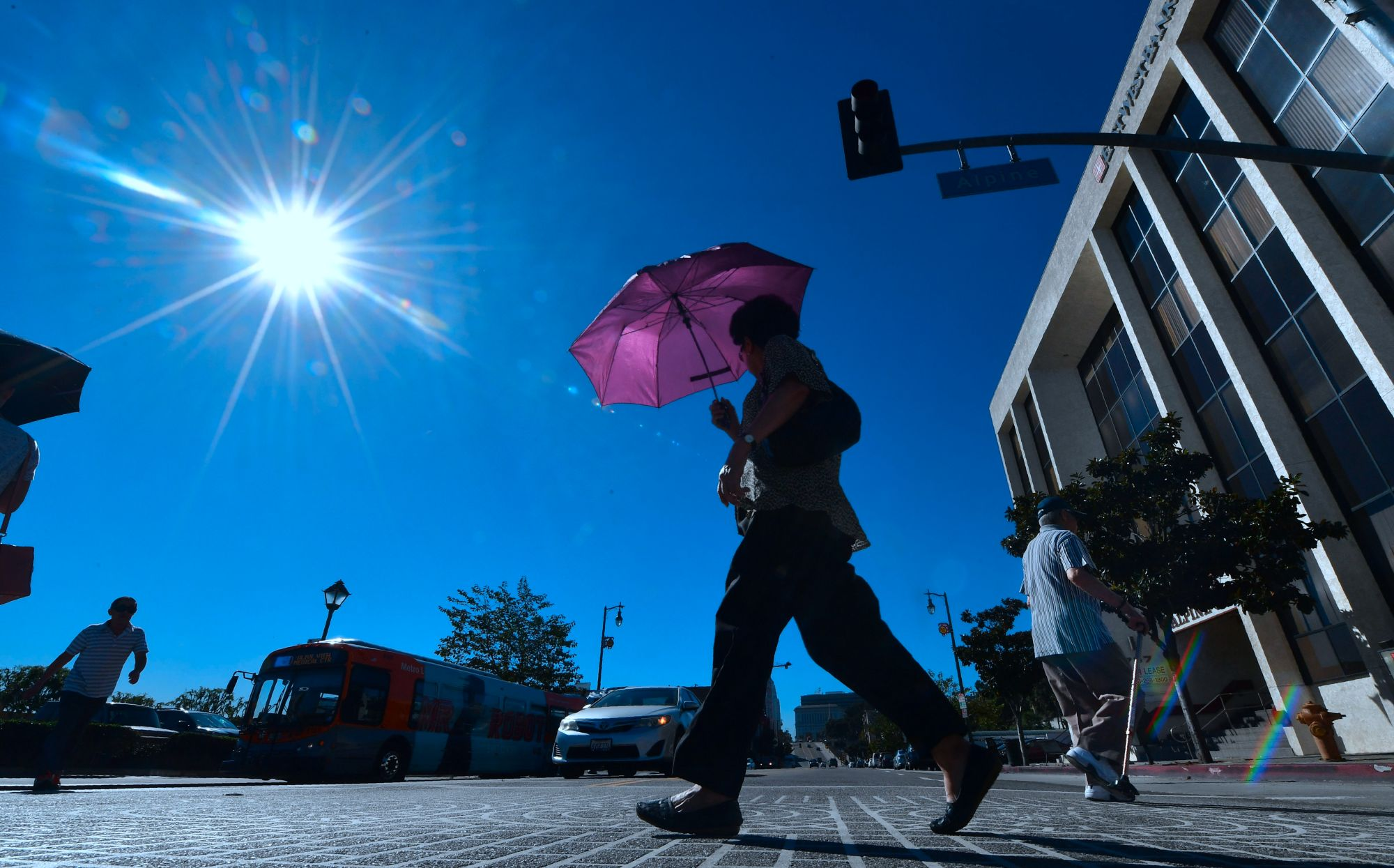 A pedestrian uses an umbrella on a hot sunny morning in Los Angeles in this file photo. (FREDERIC J. BROWN/AFP via Getty Images)