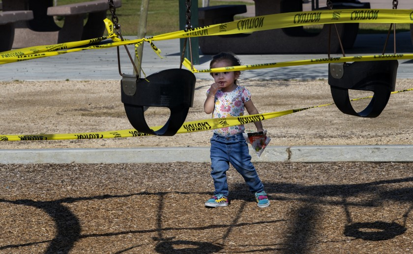 Adeline Hernandez seems perplexed by the yellow caution tape as she approaches the closed-off swing sets at Ryan Bonaminio Park in Riverside in April. (Gina Ferazzi/ Los Angeles Times)