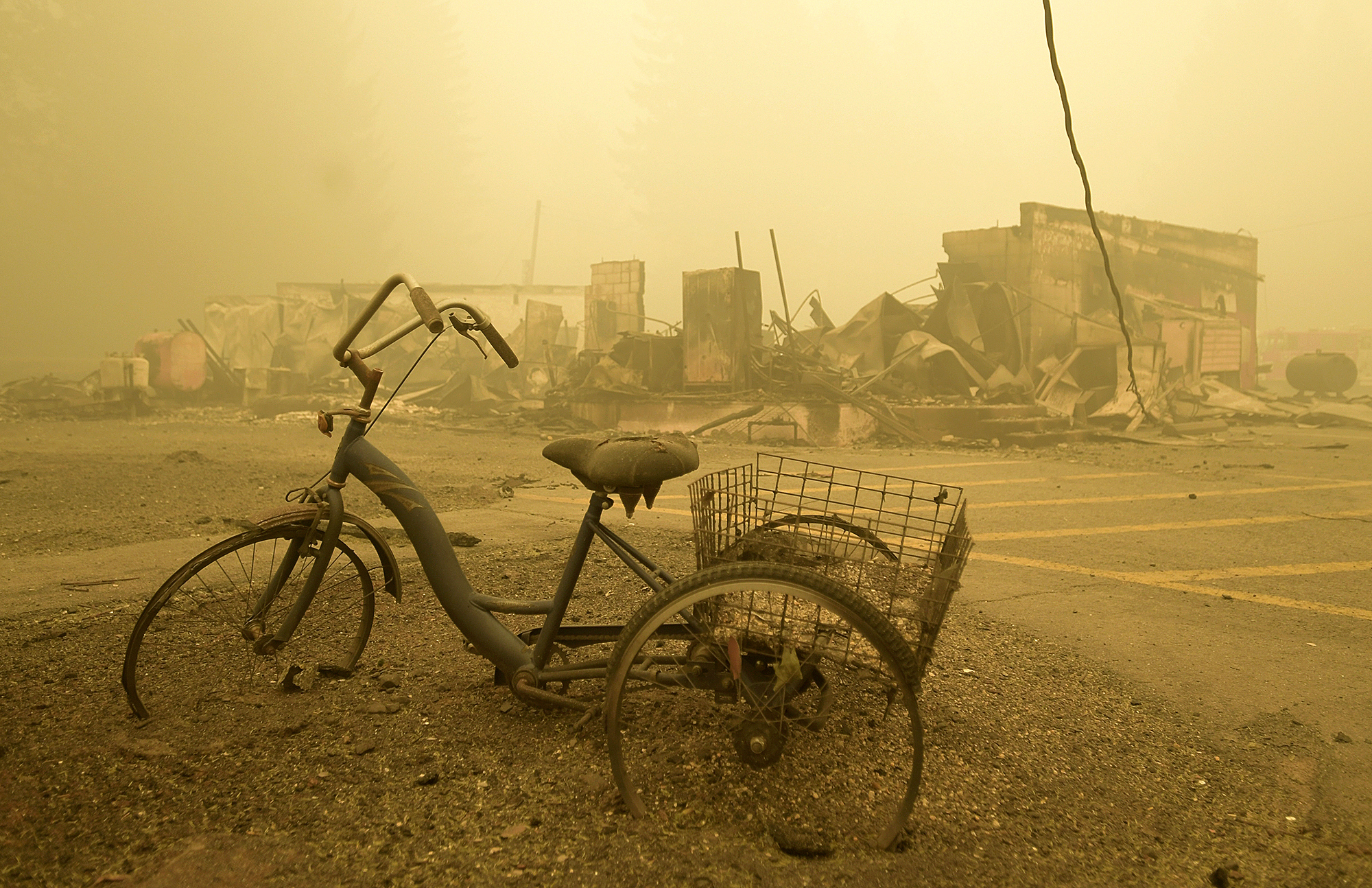 In this Sept. 11, 2020 file photo, a trike stands near the burnt remains of a building destroyed by a wildfire near the Lake Detroit Market in Detroit, Ore. The blaze was one of multiple fires that burned across the state last month. Three Pacific Northwest law firms have filed a class action lawsuit against Pacific Power and its parent company, Portland-based PacifiCorp, alleging that the power company failed to shut down its power lines despite a historic wind event and extremely dangerous wildfire conditions. (Mark Ylen/Albany Democrat-Herald via AP, File)