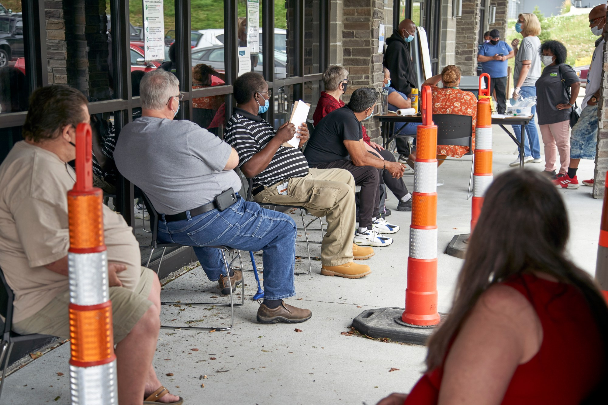 In this July 15, 2020, file photo, job seekers socially distance as they wait to be called into the Heartland Workforce Solutions office in Omaha, Neb. For the first time in nearly 50 years, older workers are facing higher unemployment than mid-career workers, according to a study released on Oct. 20, 2020. (Nati Harnik/Associated Press)