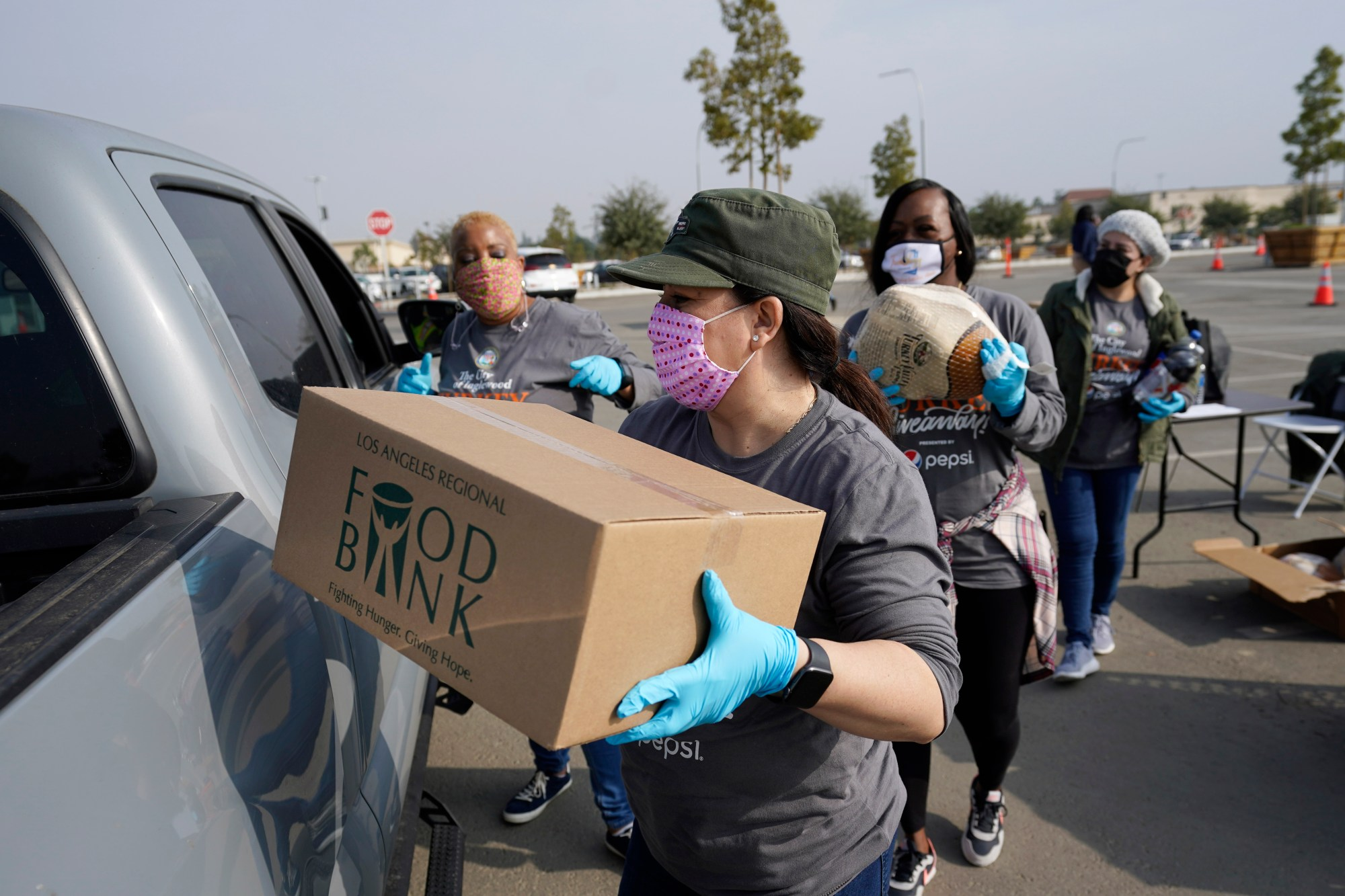 Volunteers load a pickup truck at a food distribution center set up at SoFi Stadium ahead of Thanksgiving and amid the COVID-19 pandemic, Monday, Nov. 23, 2020, in Inglewood, Calif. (AP Photo/Marcio Jose Sanchez)