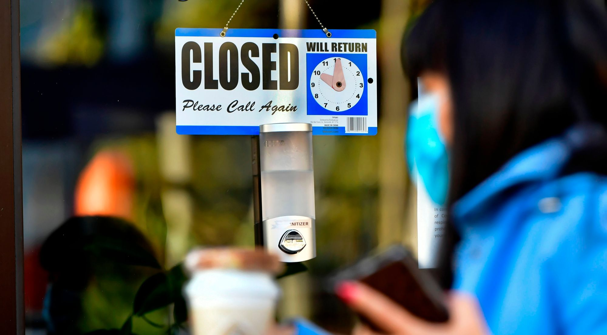 A pedestrian wearing her facemask and holding a cup of coffee walks past a closed sign hanging on the door of a small business in Los Angeles on Nov. 30, 2020. (Frederic J. Brown / AFP / Getty Images)