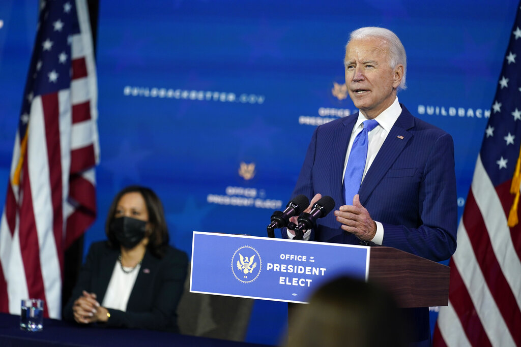 In this Dec. 1, 2020, photo, President-elect Joe Biden speaks as Vice President-elect Kamala Harris listens at left, during an event to introduce their nominees and appointees to economic policy posts at The Queen theater in Wilmington, Del. (AP Photo/Andrew Harnik)