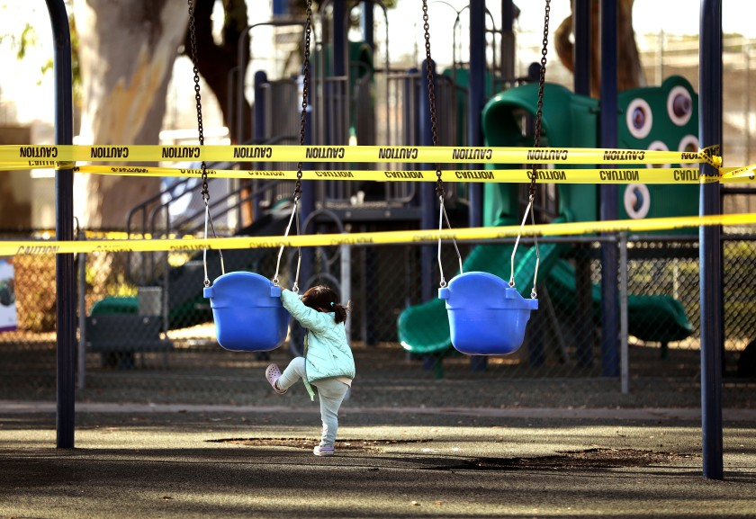 Maala Sampath, 2, tries to climb into a swing before her nanny reminds her that the playground is closed at Glen Anderson Park in Redondo Beach on Dec. 1, 2020. (Christina House / Los Angeles Times)