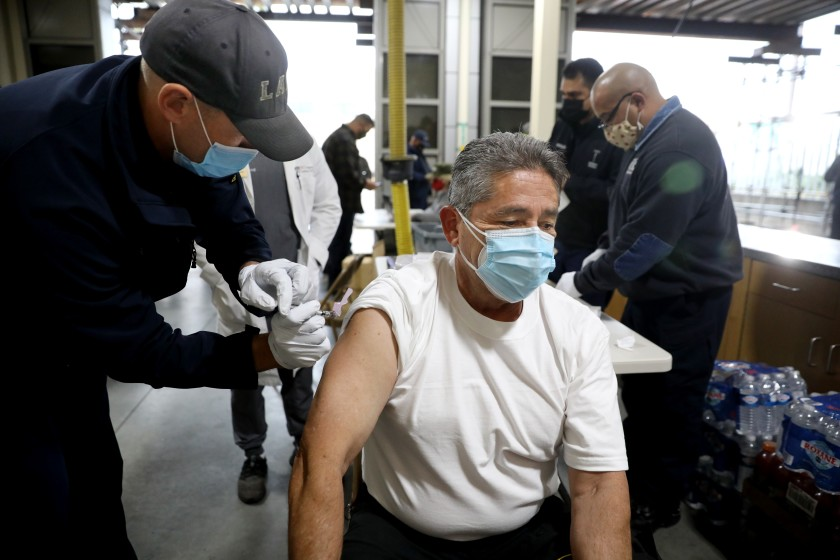 Firefighter paramedic Matthew Kovar, left, administers a COVID-19 vaccination to fire inspector Gabriel Orona at the Los Angeles Fire Department Station 4 on Dec. 28, 2020. (Gary Coronado / Los Angeles Times)