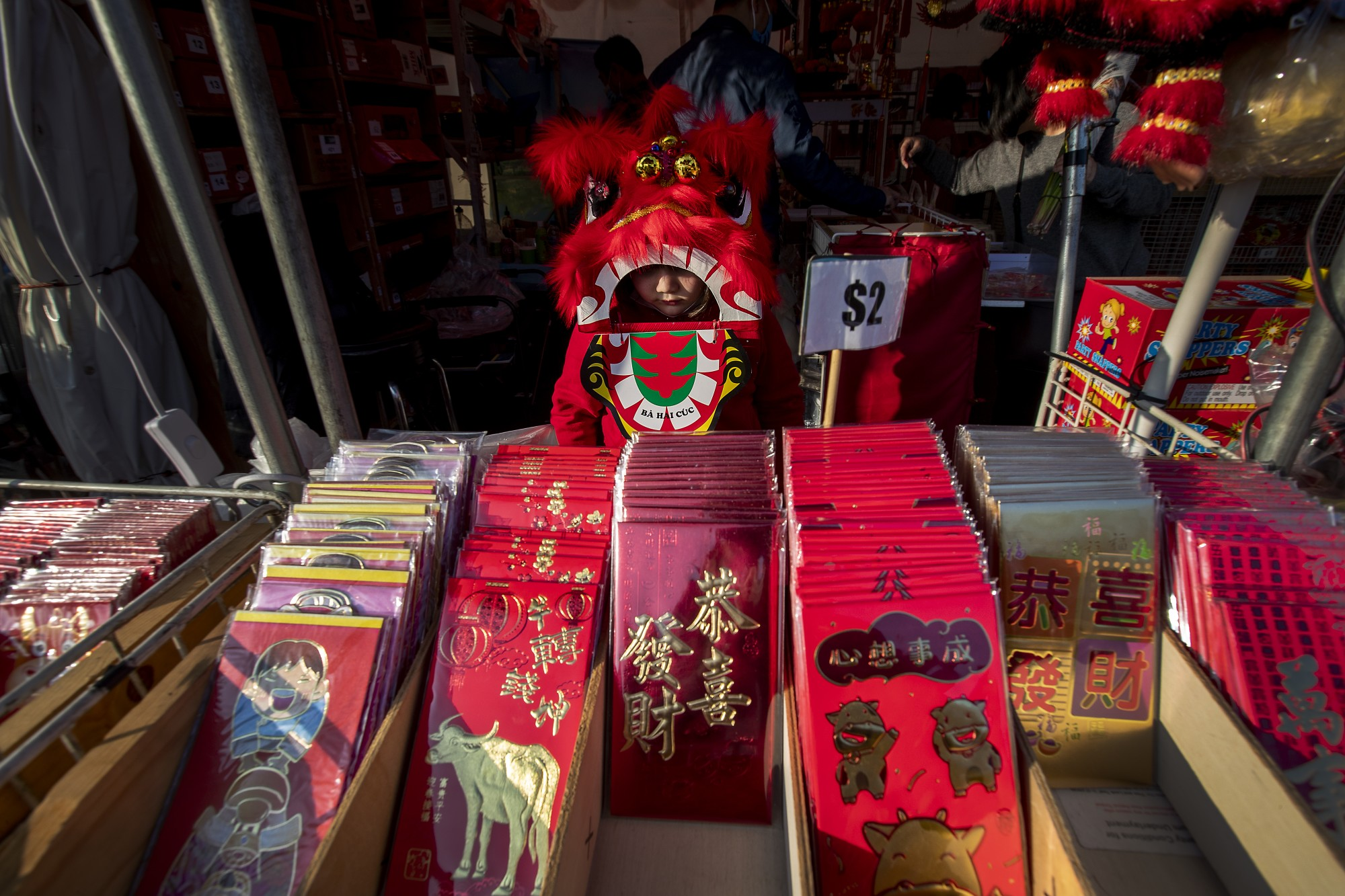 Midori Nguyen, 5, of Westminster wears a lion dance costume while looking over li xi, red envelopes for monetary gifts during holidays, at the Asian Garden Mall in Little Saigon in an undated photo.(Allen J. Schaben / Los Angeles Times)