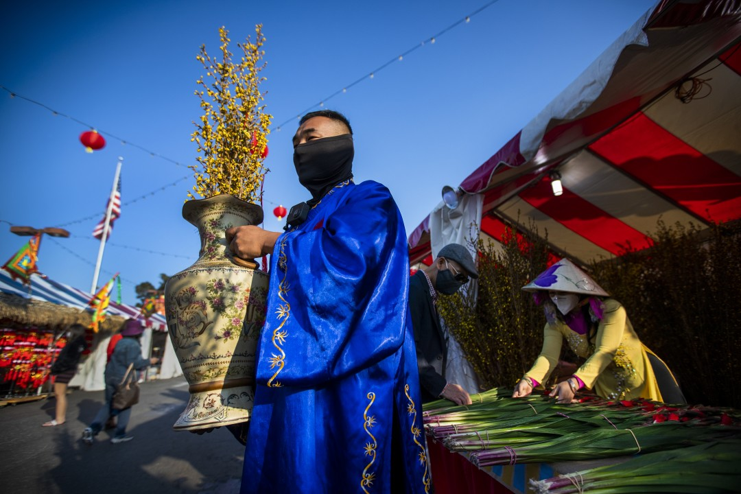 Wearing the ao dai, a traditional Vietnamese dress outfit, Jimmy Huynh, center, greets people while Stephanie Vu, right, helps a customer pick out flower in an undated photo. (Allen J. Schaben / Los Angeles Times)