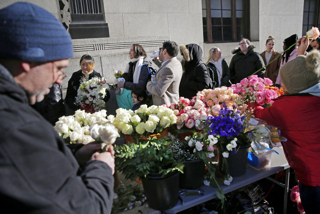 In this Feb. 14, 2020 file photo, florists prepare bouquets as people wait in a long line to enter the New York City Marriage Bureau, on Valentine's Day. (AP Photo/Seth Wenig)