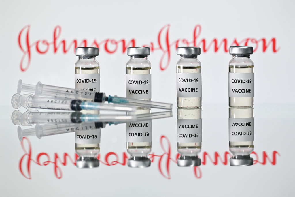 An illustration picture shows vials with Covid-19 Vaccine stickers attached and syringes with the logo of US pharmaceutical company Johnson & Johnson on November 17, 2020. (JUSTIN TALLIS/AFP via Getty Images)