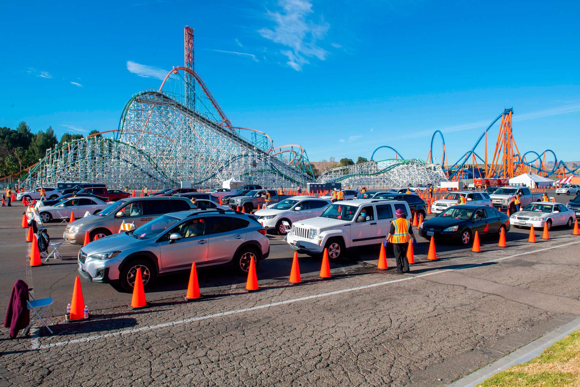 People sit in their cars in an observation area where they are checked for possible side effects after getting their vaccine shot at the large scale COVID-19 vaccination center set up at Six Flags Magic Mountain on Feb. 2, 2021 in Valencia. (VALERIE MACON/AFP via Getty Images)