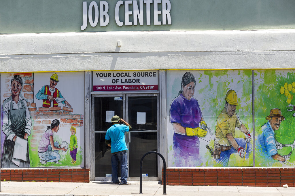 In this May 7, 2020, file photo, a person looks inside the closed doors of the Pasadena Community Job Center in Pasadena. (AP Photo/Damian Dovarganes, File)