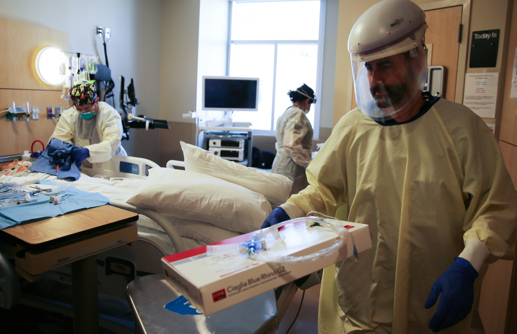 Clinicians work after performing a tracheostomy on a patient in a COVID-19 ICU at Providence Holy Cross Medical Center in Mission Hills on Feb. 17, 2021. (Mario Tama/Getty Images)