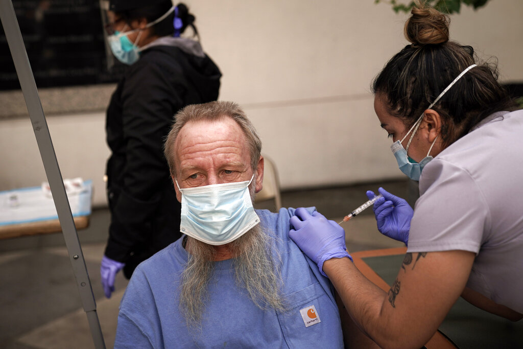 In this Feb. 3, 2021, file photo, EMT Rachel Bryant, right, administers a COVID-19 vaccine to a homeless man in the courtyard of the Midnight Mission in Los Angeles. (AP Photo/Jae C. Hong)