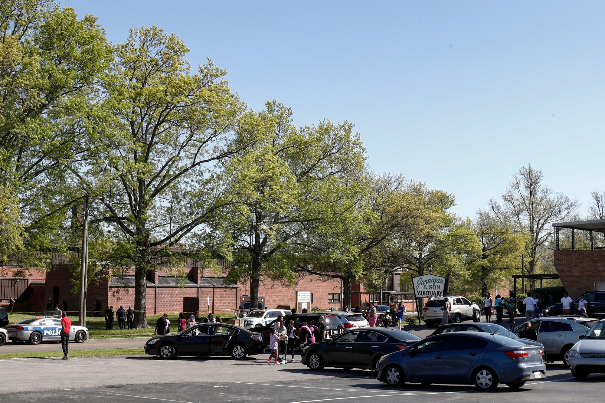 People gather outside Austin-East Magnet High School in Knoxville, Tenn., as Knoxville police work the scene following a shooting at the school Monday, April 12, 2021. (AP Photo/Wade Payne)