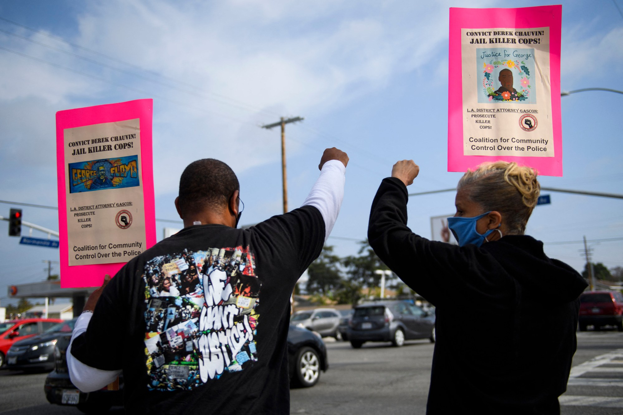 Activist Najee Ali, left, protests the killings of people by police including the death of George Floyd and Daunte Wright on April 12, 2021, at the intersection of Florence and Normandie in Los Angeles. (Patrick T. Fallon / AFP / Getty Images)