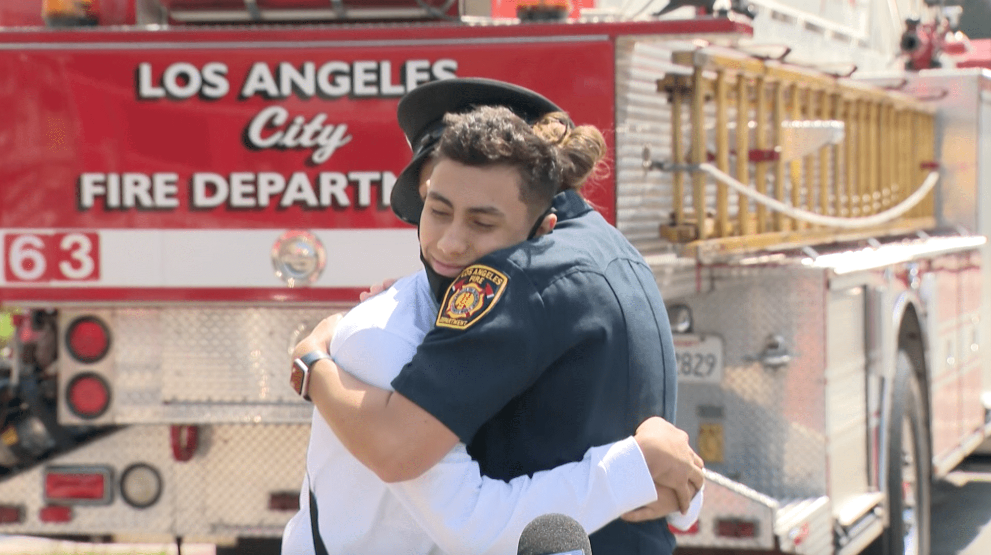 Jacob Perez, 14, hugs the dispatcher who helped save his life in Venice on April 18, 2021. (KTLA)