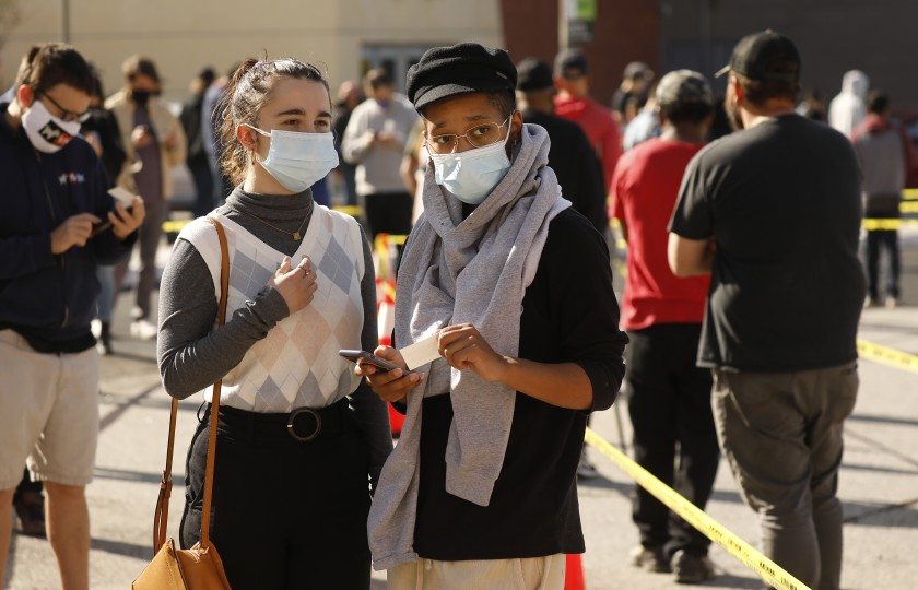 Alex Harris, right, waits in line with a friend for COVID-19 vaccination at Cal State Los Angeles on April 9, 2021. (Al Seib / Los Angeles Times)