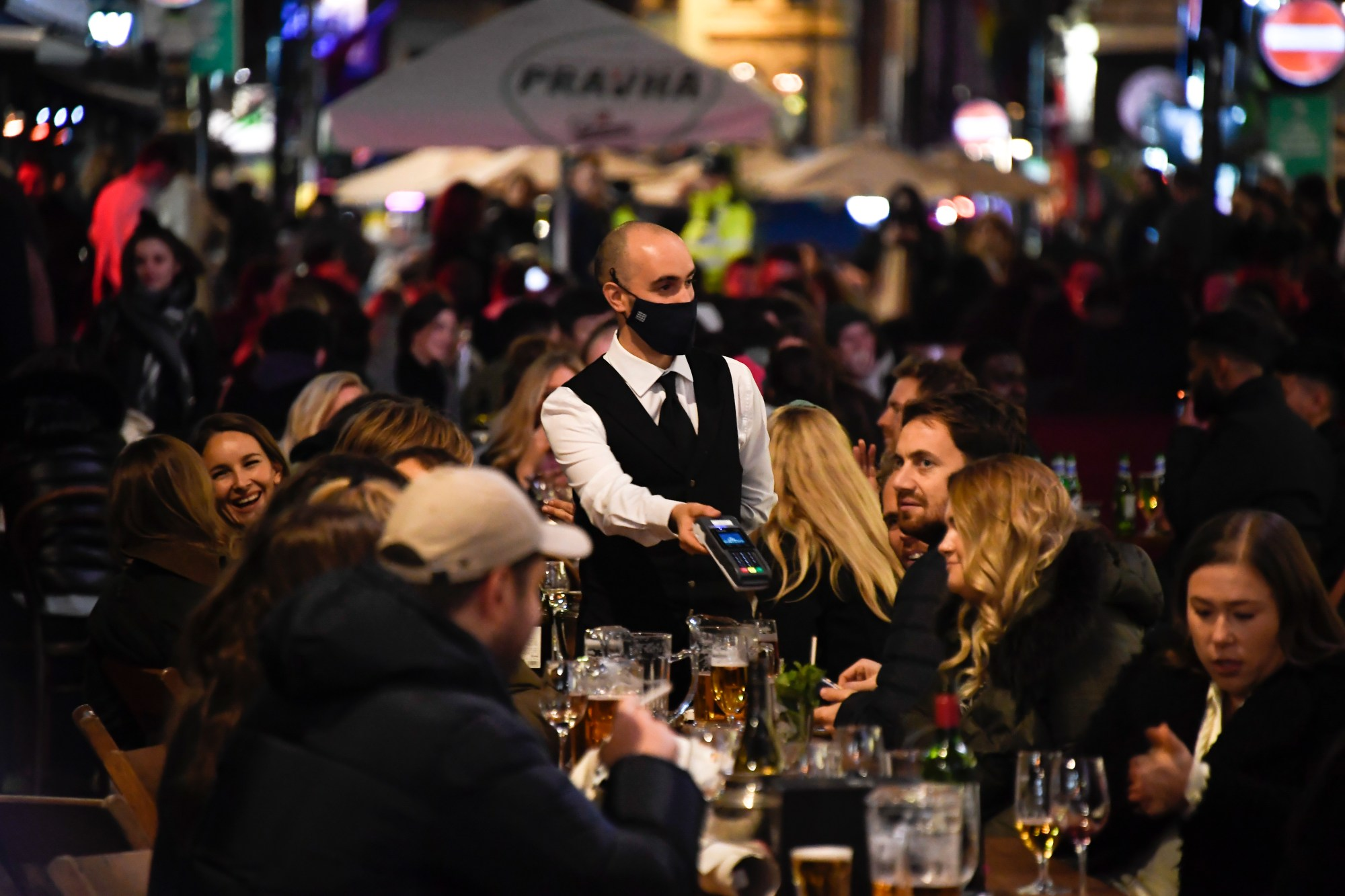 In this Wednesday, Nov. 4, 2020 file photo, a waiter wears a face mask as people eat and drink outside restaurants in Soho, in London. British Prime Minister Boris Johnson is expected to confirm Monday June 14, 2021, that the next planned relaxation of coronavirus restrictions in England will be delayed as a result of the spread of the delta variant first identified in India. (AP Photo/Alberto Pezzali, File)