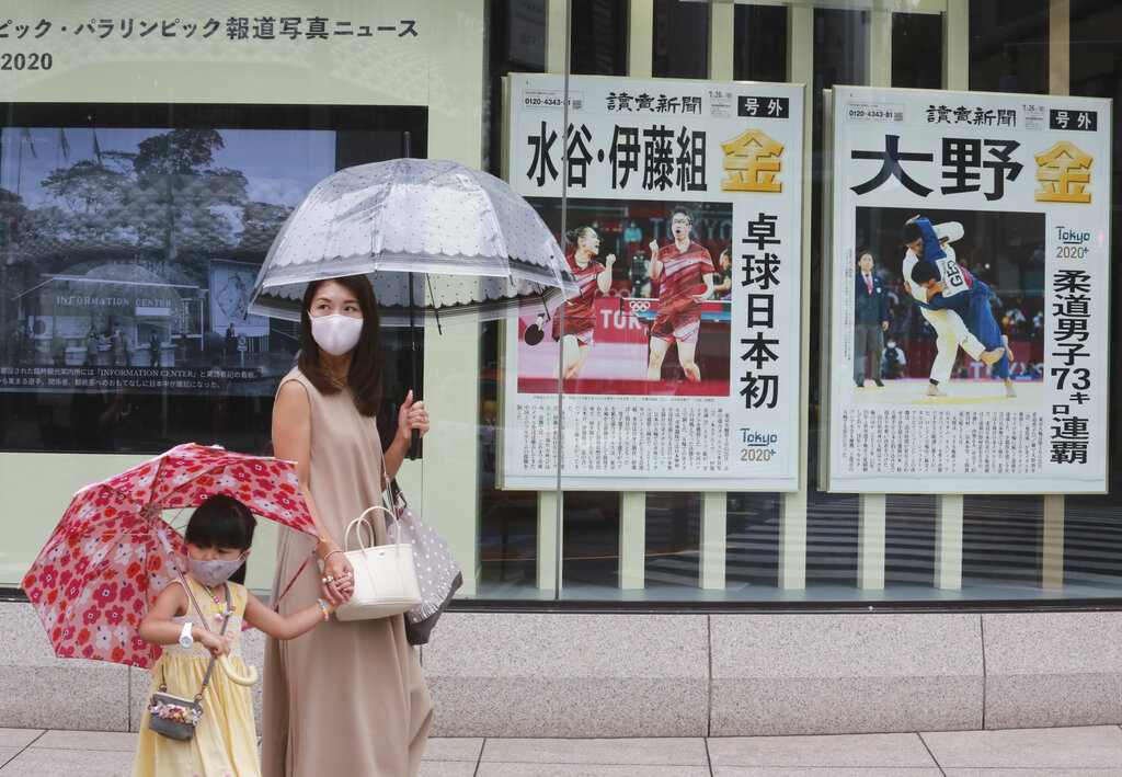 People wearing face masks to protect against the spread of the coronavirus walk past extra papers reporting on Japanese gold medalists at Tokyo Olympics, in Tokyo Tuesday, July 27, 2021. (AP Photo/Koji Sasahara)