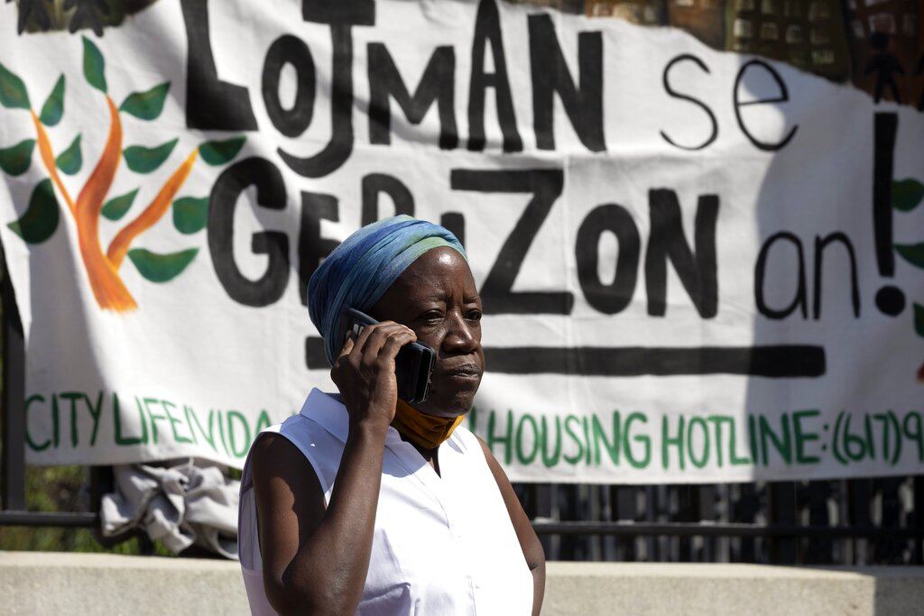 A woman speaks on the phone in front of a sign in Haitian Creole during a news conference held by a coalition of housing justice groups to protest evictions, Friday, July 30, 2021, outside the Statehouse in Boston. (AP Photo/Michael Dwyer)