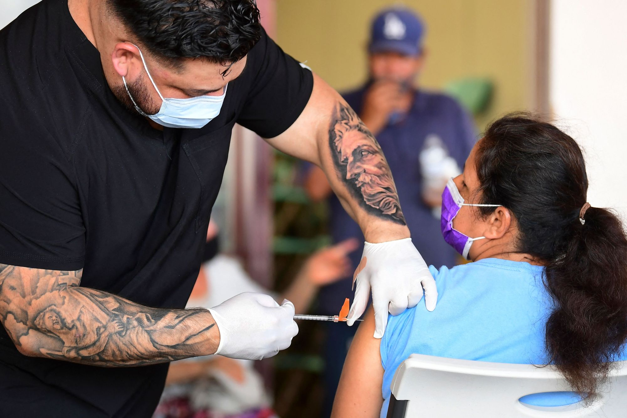 The Pfizer COVID-19 vaccine is administered at a mobile clinic to residents in an East Los Angeles neighborhood. (FREDERIC J. BROWN/AFP via Getty Images)