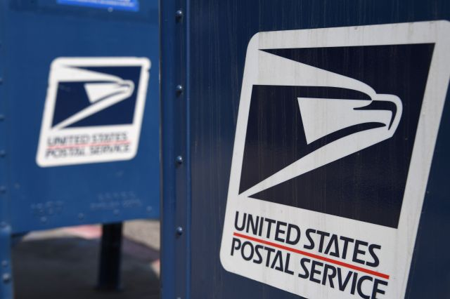 The logo of the United States Postal Service appears on a mailbox outside a post office in Los Angeles, California on August 17, 2020.  (Rubyback / AFP via Getty Images)