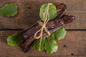 Raw fruits Carob on old wooden background