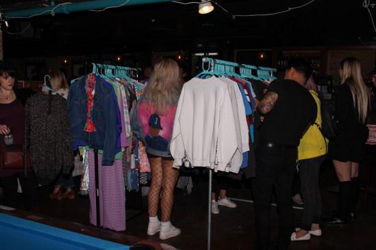People browsing Oddball Vintage's clothing racks.