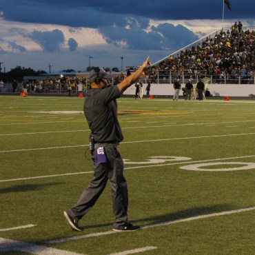 A man making a call at a high school football game.